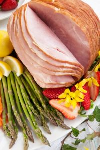 table set with festive glazed ham, asparagus, carrots, strawberry, and lemon wedges